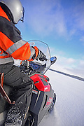 Antti, young Finnish guide from VisitInari, rides a snowmobile in the wilderness of Inari, Lapland, Finland