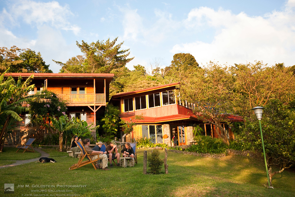A family relaxes at sunset in front of the Arco Iris Lodge in Santa Elena, Costa Rica