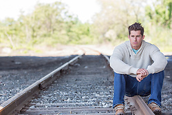 handsome man sitting on a railroad track