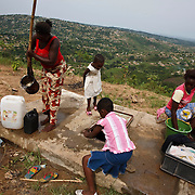 Kinshasa, DRC. 15 March 2009. Gladys Madaune with two daughters nine year old Joyce and six year old Gladale, helps her sister with the weekly wash.  Neighbours collect water from the rain water tank dug into the hill-side on the outskirts of Kinshasa. In December 2008, Gladys, along with another woman became the first two female drivers in the UNICEF DRC country office.  Having worked for many years as a mechanic with Toyota, she is well qualified for the job.