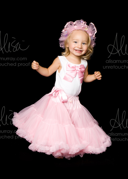 Childhood portrait photo in pink tutu on black background.