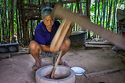 A farmer uses a home mill to process  Green (or early) Rice, Nakhon Nayok, Thailand.