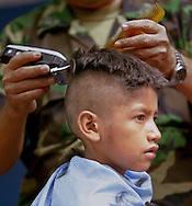COMALAPA, CHALATENANGO, EL SALVADOR- MAY 2000:  A young boy has his hair cut at a Federal military camp in Comalapa, El Salvador. (Photo by Robert Falcetti). .