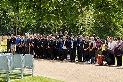 Hyde Park, London, July 7th 2015. Staff involved with the proceedings ahead of a memorial service for the victims of the 7/7 bombings at the Hyde Park memorial, hold a minute's silence at 11.30 am.