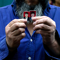 URUMQI, JULY-15 :<br /> Nurmen Met holds photographs of his sons, 19 and 21, who he said had been taken by riot officers as they entered the public bathhouse his family owns.