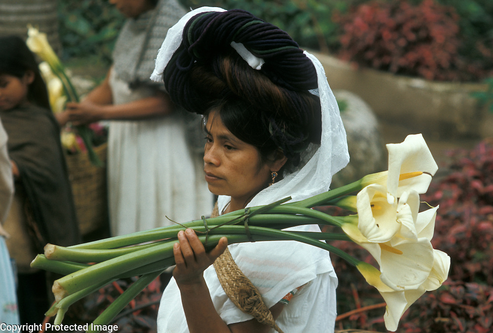Mexico, Puebla State: Indian woman with calla lily flowers at Sunday market in small town: Cuetzalan.