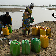 Female members of the Ouedraogo household collecting water from a dam on 27 February 2014. Each round trip takes over an hour, and typically three trips are made in a day.