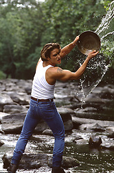 man in a stream throwing water from a pan