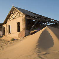 Africa, Namibia, Kolmanskop, Drifting sand dunes fill decaying buildings in ghost town of abandoned diamond mining town
