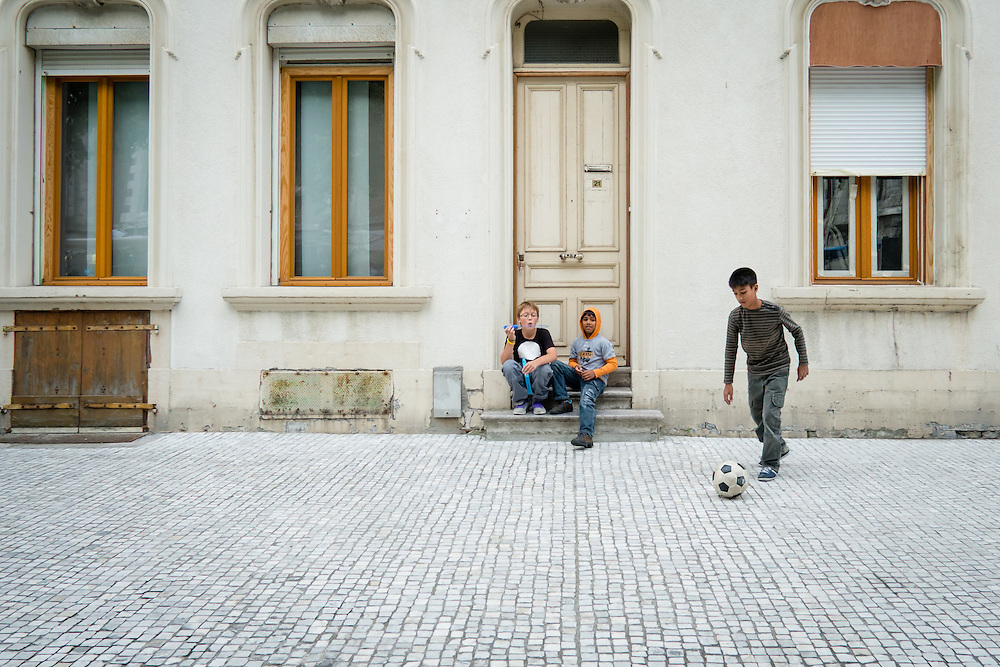 Boy playing football in the streets of Calais, Normandy, France