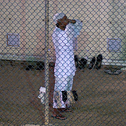 "A detainee performs the Muslim call to prayer for the rest of detainees in Camp 4 at the detention facility in Guantanamo Bay, Cuba. Camp 4 is a communal style camp where more compliant detainees live in small groups and have access to a more open air environment. Approximately 250 ""unlawful enemy combatants"" captured since the September 11, attacks on the United States continue to be held at the detention facility.(Image reviewed by military official prior to transmission)"