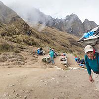 Peru, Porter carries heavy load at 13,800' summit of Dead Woman's Pass along Inca Trail to Machu Picchu along Urubamba River