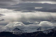 The sun shines through heavy storm clouds over Skarðsheiði, a 1041 meter (3415 feet) mountain range near Borgarnes, Iceland.