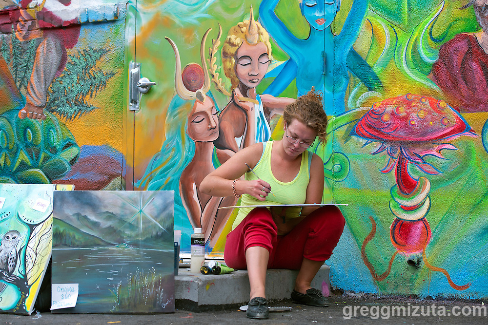 Morgan Mae Cleverly works on a painting in front of her mural in the evening of August 13, 2016 during the Freak Alley Gallery sixth annual mural event in downtown Boise, Idaho.<br /> <br /> Freak Alley Gallery's week long event provided an &quot;art-in-motion&quot; experience as it welcomed the public to watch artists work on their murals.