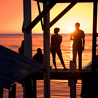 Divers watch the sun go down from a dock in front of a Dive Shop in the West <br /> End. Roatan, Honduras.