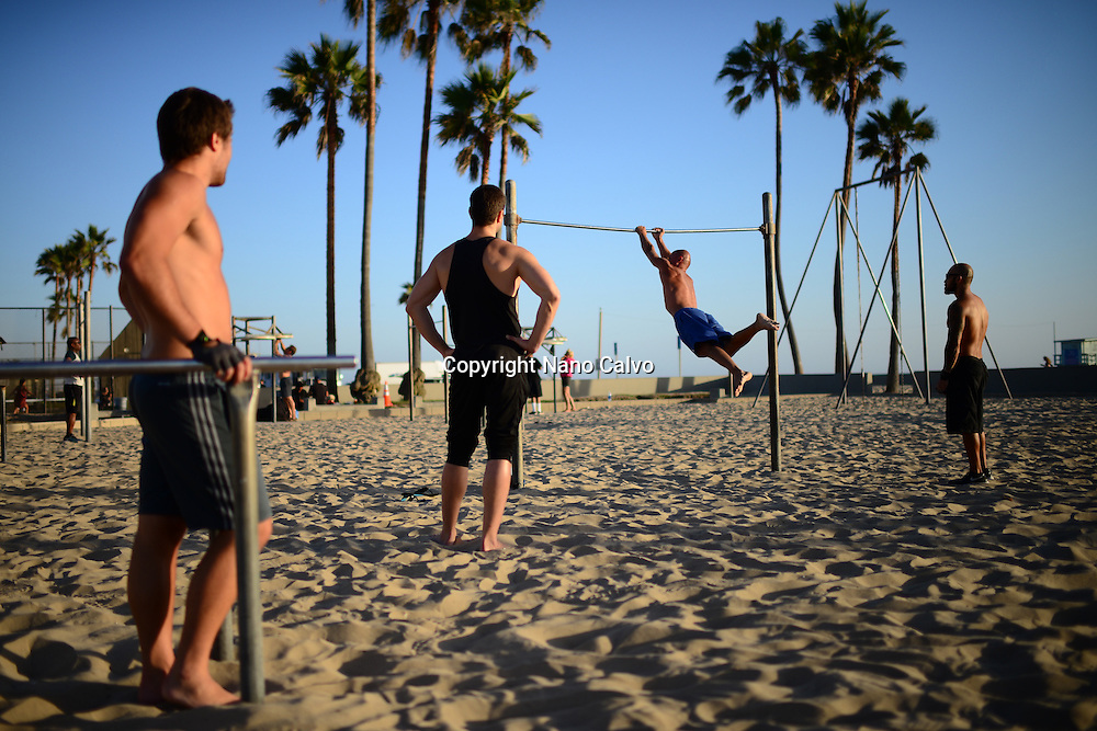 Group of young men practicing in Venice Beach Calisthenics park, California.