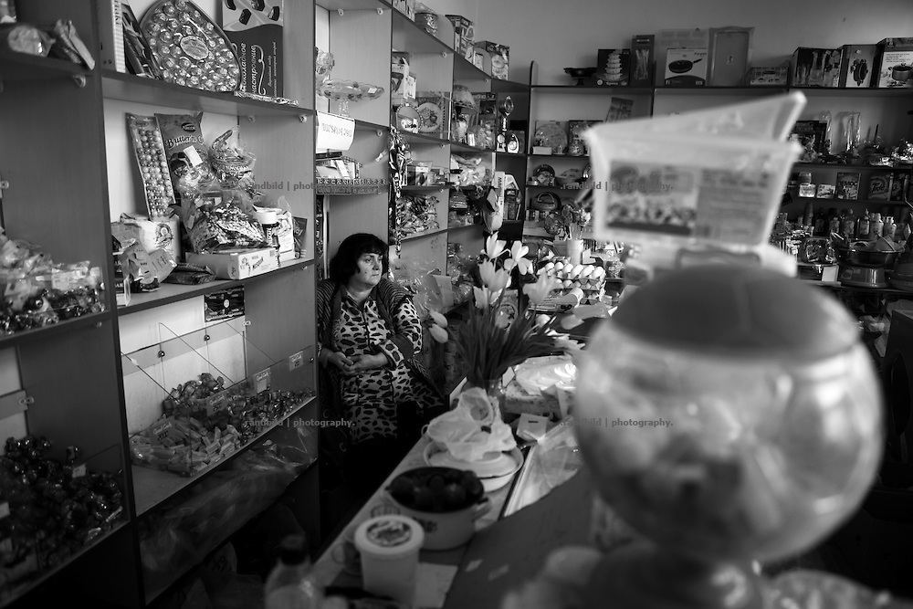 "An owner in her grocery waits for costumers.. This image is part of the photoproject ""The Twentieth Spring"", a portrait of caucasian town Shushi 20 years after its so called ""Liberation"" by armenian fighters. In its more than two centuries old history Shushi was ruled by different powers like armeniens, persians, russian or aseris. In 1991 a fierce battle for Karabakhs independence from Azerbaijan began. During the breakdown of Sowjet Union armenians didn´t want to stay within the Republic of Azerbaijan anymore. 1992 armenians manage to takeover ""ancient armenian Shushi"" and pushed out remained aseris forces which had operate a rocket base there. Since then Shushi became an ""armenian town"" again. Today, 20 yeras after statement of Karabakhs independence Shushi tries to find it´s opportunities for it´s future. The less populated town is still affected by devastation and ruins by it´s violent history. Life is mostly a daily struggle for the inhabitants to get expenses covered, caused by a lack of jobs and almost no perspective for a sustainable economic development. Shushi depends on donations by diaspora armenians. On the other hand those donations have made it possible to rebuild a cultural centre, recover new asphalt roads and other infrastructure. 20 years after Shushis fall into armenian hands Babies get born and people won´t never be under aseris rule again. The bloody early 1990´s civil war has moved into the trenches of the frontline 20 kilometer away from Shushi where it stuck since 1994. The karabakh conflict is still not solved and could turn to an open war every day. Nonetheless life goes on on the south caucasian rocky tip above mountainious region of Karabakh where Shushi enthrones ever since centuries."