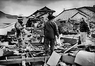 Ofunato resident, standing upon the rubble of his house, talks with rescue worker, Iwate Prefecture, Japan.  Families can be seen rummaging through the remains of their homes, looking for momentos and family valuables.