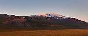 """The last light of day illuminates Snæfellsjökull, a 1,446 meter (4,744 foot) stratovolcano located in western Iceland. The volcano, which is active, last erupted approximately 1,800 years ago, creating lava fields at its base. The mountain is technically named Snæfell; Snæfellsjökull is the name of the glacier at its peak. It is commonly called Snæfellsjökull, however, to avoid confusing it with several other mountains with the same name. Snæfellsjökull means """"snow glacier mountain,"""" and it was featured in the 1864 novel """"A Journey to the Center of the Earth"""" by Jules Verne."""