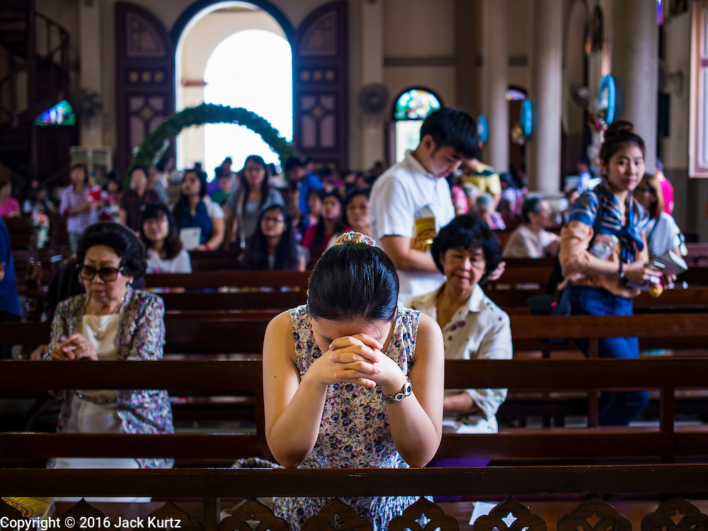 27 MARCH 2016 - BANGKOK, THAILAND: A woman prays after Easter services at Santa Cruz Church in Bangkok. Santa Cruz was one of the first Catholic churches established in Bangkok. It was built in the late 1700s by Portuguese soldiers allied with King Taksin the Great in his battles against the Burmese who invaded Thailand (then Siam). There are about 300,000 Catholics in Thailand, in 10 dioceses with 436 parishes. Easter marks the resurrection of Jesus after his crucifixion and is celebrated in Christian communities around the world.      PHOTO BY JACK KURTZ