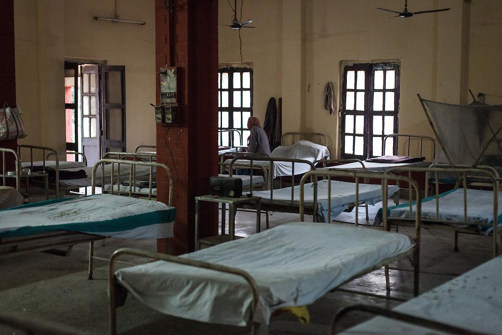 A leprosy patient sits on his hospital bed in the mens ward at the Avadhoot Bhagwan Ram Kustha Sewa Ashram