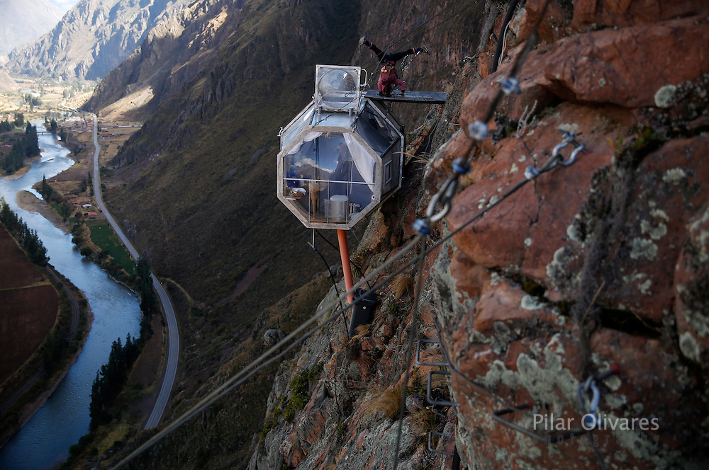 """A guest performs yoga above the sleeping pod at the Skylodge Adventure Suites in the Sacred Valley in Cuzco, Peru, August 14, 2015. Tourists taking on an arduous climb up the steep cliff face of Peru's Sacred Valley are being rewarded for their efforts by being able to spend the night in transparent mountaintop sleeping pods at the """"Skylodge Adventure Suites"""". To reach the pods, visitors need to climb 400 metres of via ferrata (a steel cable and rungs) up the valley side or hike an intrepid trail through zip lines. REUTERS/Pilar Olivares"""