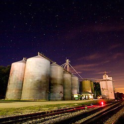 A large grain elevator complex occupies a spot next to a railroad main line under a starry night sky in the small Illinois town of Gilman.