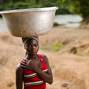 "Fuseima (13) on her way home with water from the river about a kilometre's walk from her home in the Upper West Region of Ghana on 27 May 2014. Fuseima used to go to school, but says that when ""petty dues"" needed to be paid her parents said they couldn't afford it, so she stopped going."