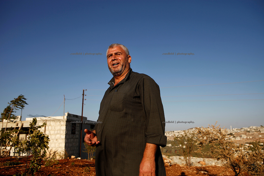 Retired police man Nadir stands in the garden in front of his new built house. Outside the village limits people use to settle on public ground and built new small houses. By doing so they seek to avoid occasional shelling by regime forces. In additionaly arranged gardens crop of vegetables support their daily living.<br />