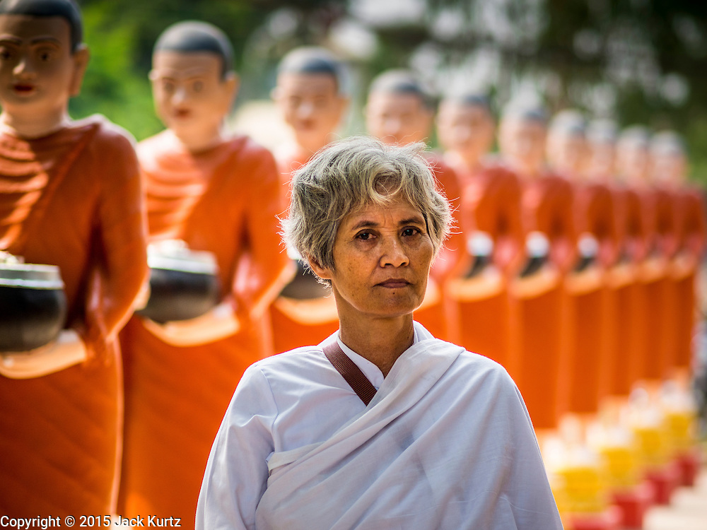15 MARCH 2015 - SIEM REAP, SIEM REAP, CAMBODIA: A woman walks among a row of statues of Buddhist monks collecting alms at the annual mass merit making at Wat Bo in Siem Reap. More than 1,200 Buddhist monks, from across Siem Reap province, received alms from Buddhist lay people during the morning long ceremony. Wat Bo was originally built to be a the temple for Siamese (Thai) troops when Siem Reap and western Cambodia were controlled by Siam (Thailand). Now Wat Bo is one of the most important temples in Siem Reap.      PHOTO BY JACK KURTZ