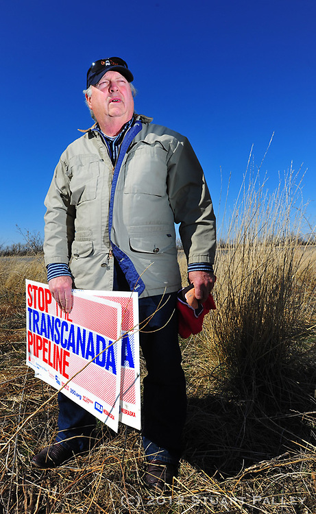"""Tom Genung of Hastings, NE poses in front of the South Branch of the Platte River. Genung is an adrent opponent of Trans Canada's failed bid to build the Keystone XL Pipeline across the Nebraska Sandhills and Ogalalla Aquifier. He is part of an informal group he calls the """"Sheriff's Posse"""" and testified in front of Nebraska's Unicameral Legislature against the Keystone Pipeline construction. Genung and his fellow Nebraskans have been successful in stopping the bid for the time being, but still face efforts from Trans Canada to expand capacity to pump hot tar sands from Alberta, Canada South to oil refiniders in Houston and the Gulf Coast area."""