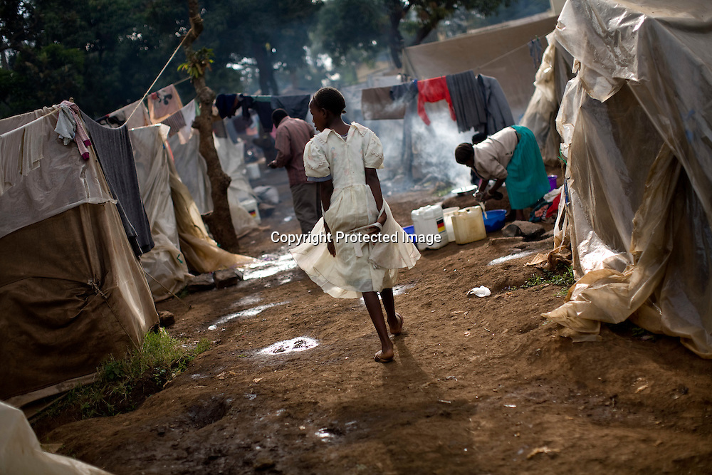 A girl makes her way along a row of tents at a Red Cross-run camp in the Mathare section of Nairobi, May 25, 2008. More than 300,000 Kenyans were left homeless after President Mwai Kibaki's disputed re-election in December triggered ethnic clashes, killings and looting. Some aid workers estimate that half of them have returned home, but many are still too afraid or don't have enough resources to do so despite reassurances from the power-sharing government.