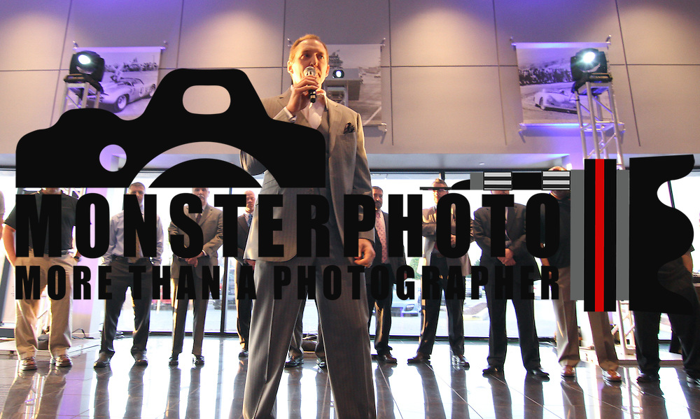 Porsche of Delaware President Michael Hynansky (Center) addresses the audience during a Porsche Cayman S Unveiling event Thursday, May. 2, 2013, at  Porsche of Delaware in Newark Delaware.