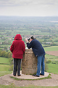 A man with binoculars and a woman survey the landscape from Coaley peak with views across the Severn valley to the Brecon Beacons in Wale in the Distance