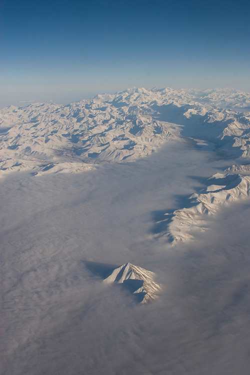 An aerial view of the Alaska Range blanketed with white fog below and deep blue sky above.
