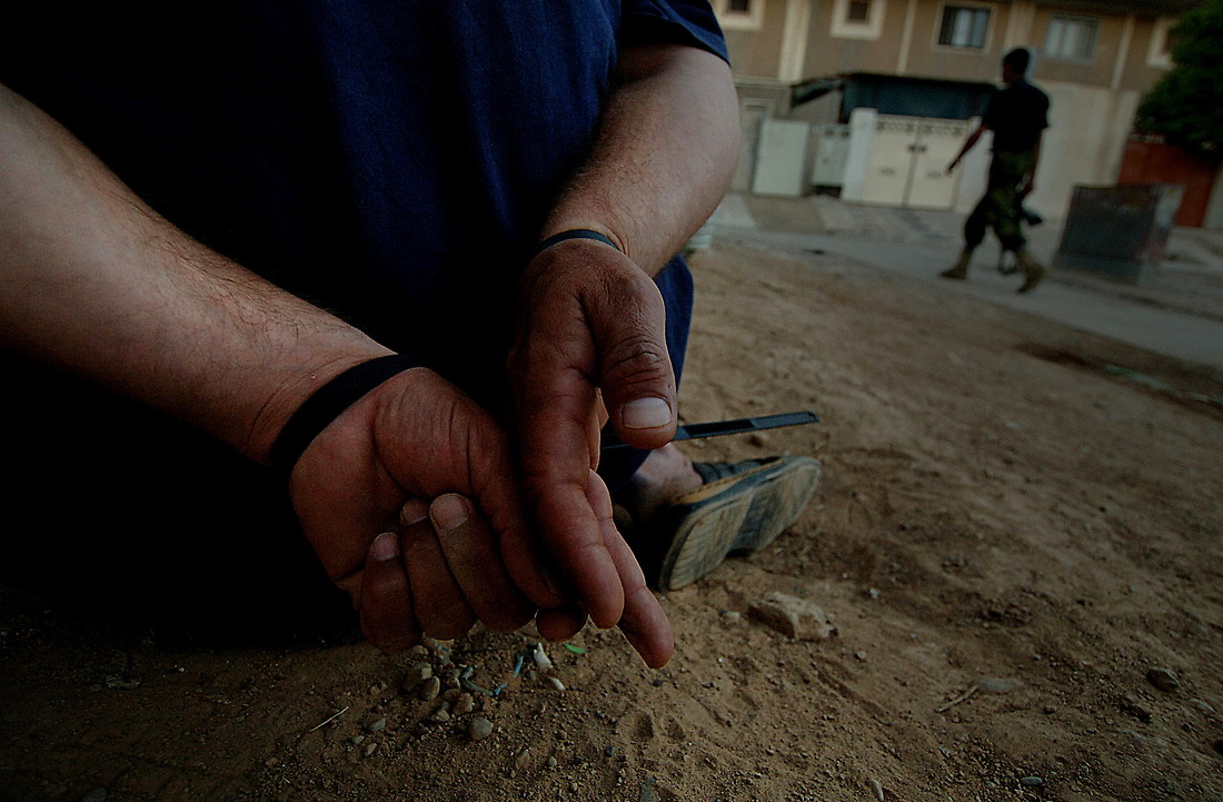 A detainee caught in an early morning raid on June 1, 2006 at the Khadra Apartments, Mosul, Iraq sits cuffed while the others caught are being questioned. The raid was led by the Iraqi Police 1st Emergency Response Battalion and the 2/4 Iraqi Army BN supported by soldiers from Charlie Company 2-1 Infantry 172nd Stryker BDE Ft. Wainwright, Alaska. During the raid three terrorist were detained, one was a Battalion Commander for the Army of Resistance and another was a high ranking official for al-Qaida. — © TSgt Jeremy Lock/