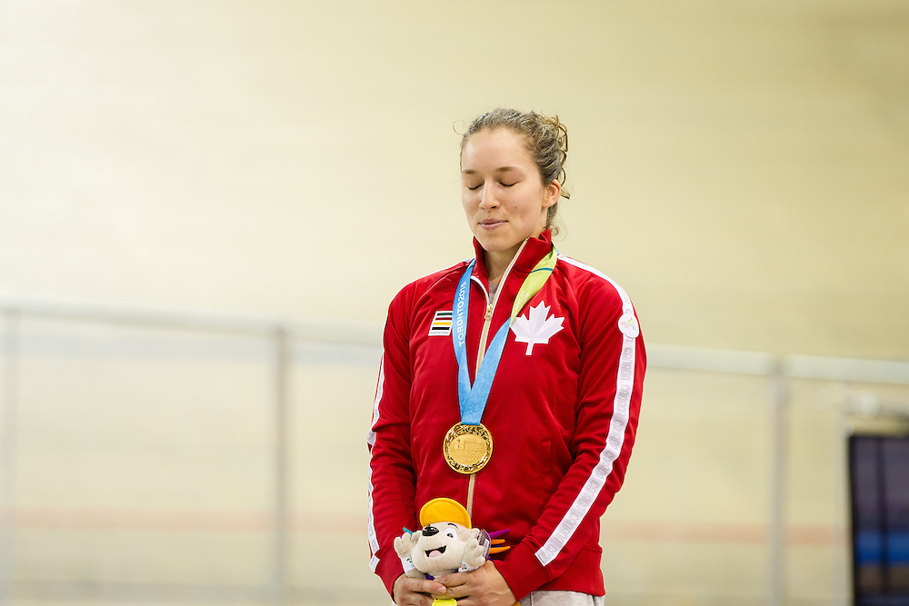 Gold medalist Monique  Sullivan of Canada listens to her national anthem during the medal ceremony for the women's cycling sprint finals at the 2015 Pan American Games in Toronto, Canada, July 19,  2015.  AFP PHOTO/GEOFF ROBINS