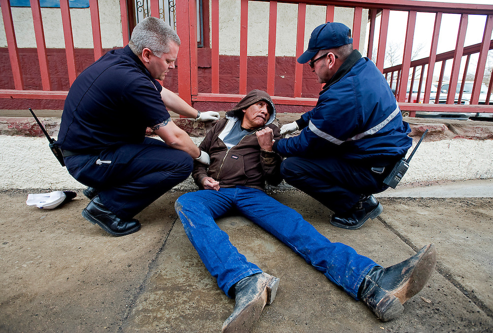 012209      Brian Leddy.Gallup Firefighters Lt. Michael Hoffman and Craig Carver assist Wes Yazzie in downtown Gallup January 22. Yazzie was found passed out along Second Street with a Listerine bottle at his side.