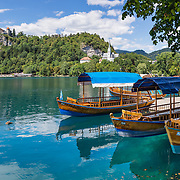 """Pletna boats carry tourists across Lake Bled under the medieval Bled Castle (Slovene: Blejski grad, German: Burg Veldes), which was built a little before 1011 AD on a cliff above the city of Bled, in what is now Slovenia, Europe. The distinctive two-paddle Pletna boats originated in 1590 and can carry 20 people. A colourful awning protects passengers from sun and weather. The respected title of """"Pletnarstvo,"""" Pletna oarsman, has been handed down within specific families from generation to generation. This panorama was stitched from 4 overlapping photos."""