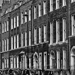Taxicabs along the curb outside an apartment building, Bloomsbury, London, England