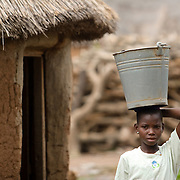 """Mariam Alhassan, 11, carries an empty bucket on her head as she prepares to head out to fetch water with other girls after coming home from school in the village of Ying, in the Savelugu-Nanton district, northern Ghana on Monday June 4, 2007. """"I saw some other children go to school,"""" she recalls, """"but my father said we had no money for me to go. I cried and he agreed to send me."""" Before heading to school, Mariam I helps her mother at home by sweeping the floor, cooking, fetching water and firewood.When her father died a few years back, her older brother promised to keep her at school.."""
