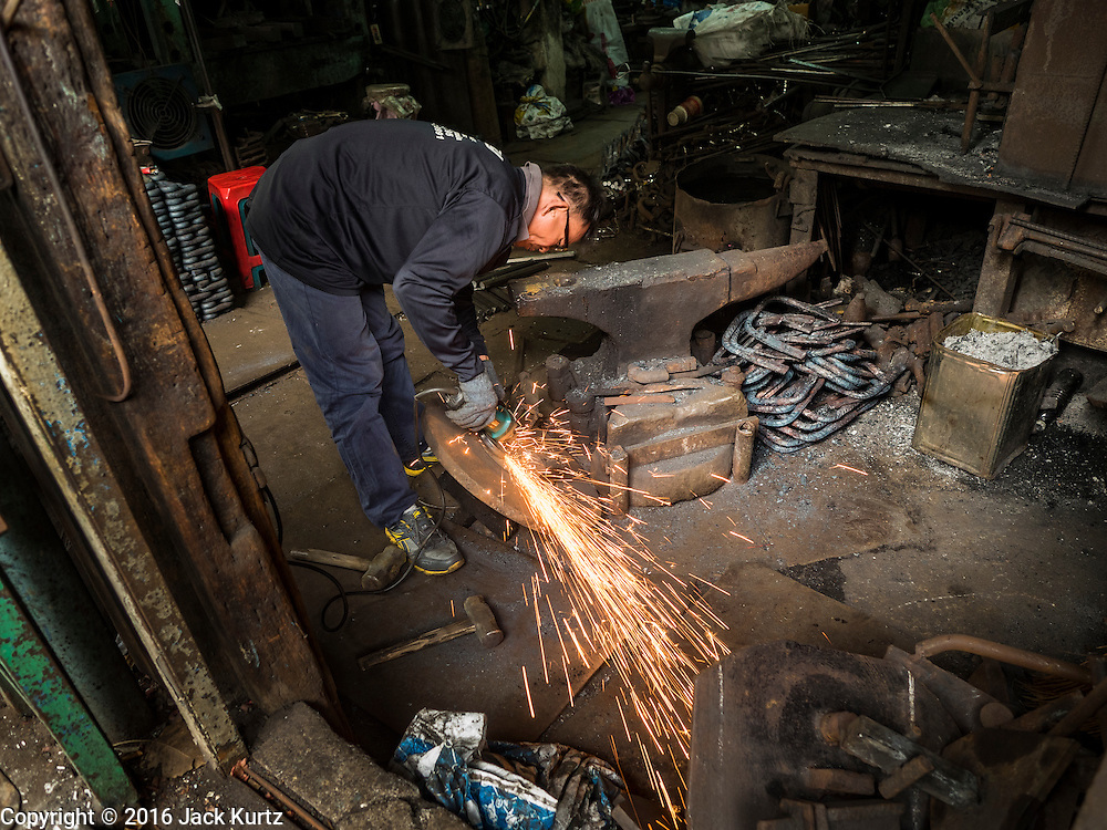 25 JANUARY 2016 - BANGKOK, THAILAND:         A worker cuts metal in a small workshop in Talat Noi, Bangkok. The one person workshop makes heavy chains for boat anchors. The metal for the chains is heated until it glows red and then it's pounded into shape. The Talat Noi neighborhood in Bangkok started as a blacksmith's quarter. As cars and buses replaced horse and buggy, the blacksmiths became mechanics and now the area is lined with car mechanics' and blacksmiths' shops.     PHOTO BY JACK KURTZ