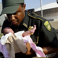 Earl Dunbar of the Louisiana State Capitol Police carries a five-day-old baby an evacuee brought for treatment near the Superdome (background) in downtown New Orleans, Louisiana August 31, 2005. The mother said she had been trapped in her home until Wednesday after Hurricane Katrina hit.  Authorities struggled on Wednesday to evacuate thousands of people from hurricane-battered New Orleans as food and water grew scarce and looters raided stores, while U.S. President George W. Bush said it would take years to recover from the devastation.  REUTERS/Rick Wilking