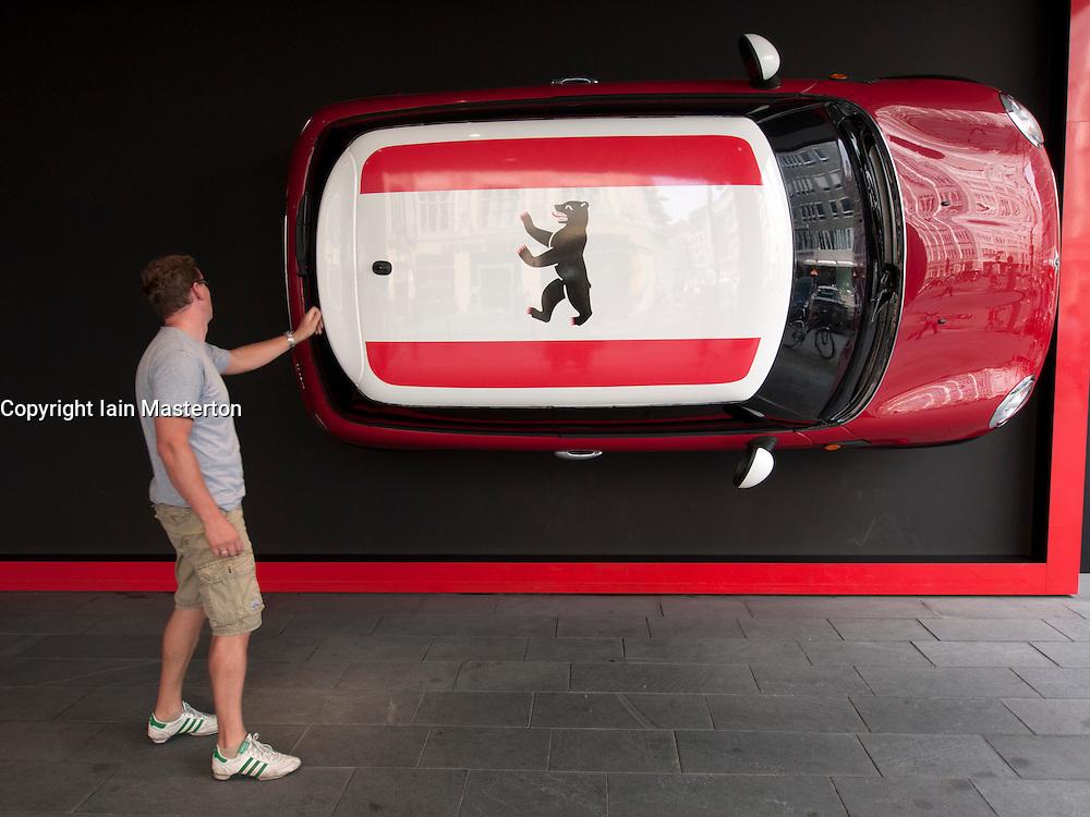 Mini motor car on wall outside Mini showroom store on Friedrichstrasse in Berlin Germany