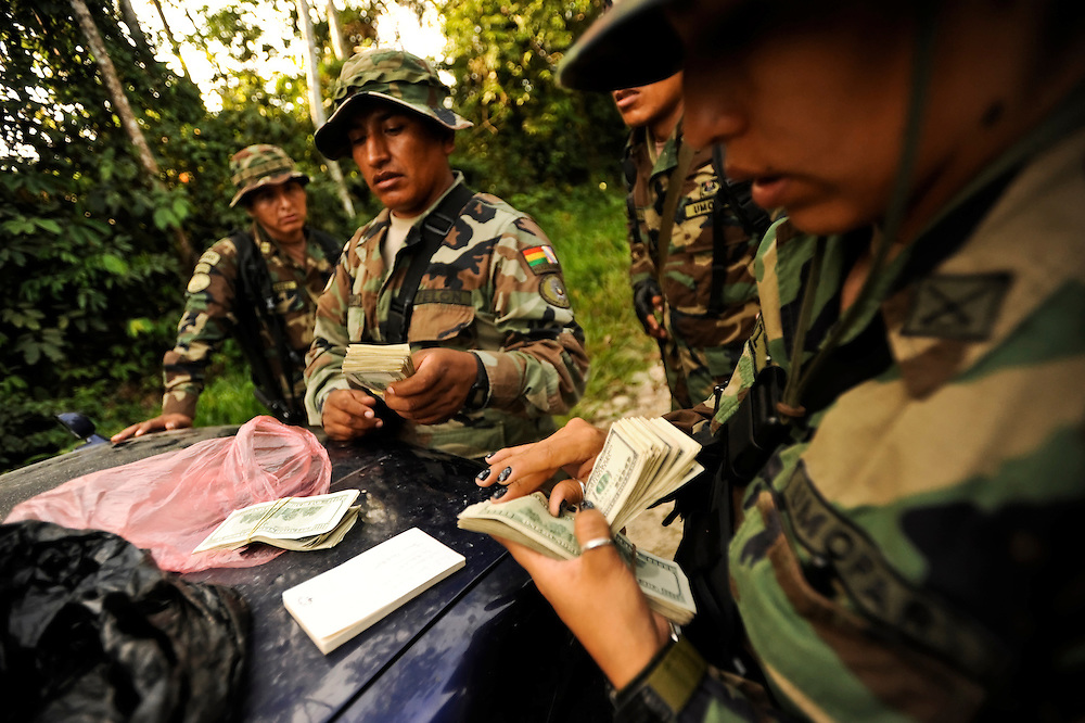 """Bolivian FELCN Special Forces count over $23,000 in US dollars found during a raid, along with 75 bags of dried coca leaves and processing materials to convert it into cocaine-base in Villa Nuevo Horizonte, a dangerous area in the department of Santa Cruz were narcotraffiking runs rampant. FELCN officials report it is the area of Bolivia most thickly dense of narcotraffickers and cocaine-base processing laboratories.  FELCN police commonly referred to it as a """"narco pueblo""""."""