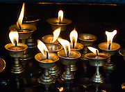 """Candles make a religious offering at Buddhist Swayambhunath, the """"Monkey Temple"""", founded about 500 AD, one of the oldest and holiest Buddhist sites in the Kathmandu Valley, Nepal. Swayambhunath sits on a hill in the west of Kathmandu overlooking the city."""