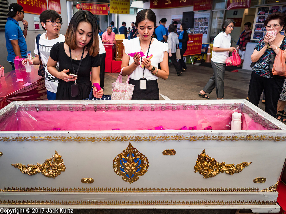 01 FEBRUARY 2017 - BANGKOK, THAILAND:  People prays and make donations into a coffin during Lunar New Year observances at the Poh Teck Tung Shrine in Bangkok. This is the Year of the Rooster in the Chinese zodiac and people pray and make merit to large statues of roosters in Chinese temples and shrines. Poh Teck Tung provides coffins for indigent people who can't afford them and donating money to Poh Teck Tung for coffins is a New Year's tradition in Bangkok.    PHOTO BY JACK KURTZ