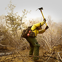 A Dalton Hotshot firefighter clears a three foot (90cm) line down to bare soil around an errant fire that has jumped the fire break. Much of the dangerous work is performed by elite ground crews in steep terrain with 55 lb. (25 kg) packs, 25 lb.(11 kg) chainsaws, shovels and rakes, and two gallons (3.78 l) of water for a ten hour shift.
