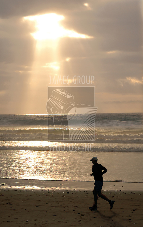 Man jogging on the beach with a sunburst in the background