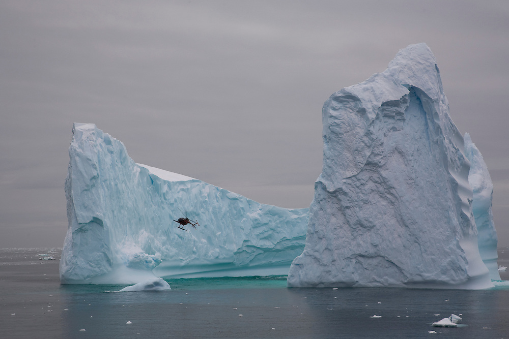 February 8th 2007. Southern Ocean. A Greenpeace helicopter flies past an iceberg in the Ross Sea.